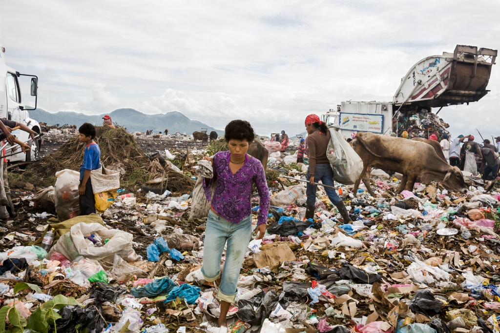 A woman carries a sack at the garbage dump La Chureca.