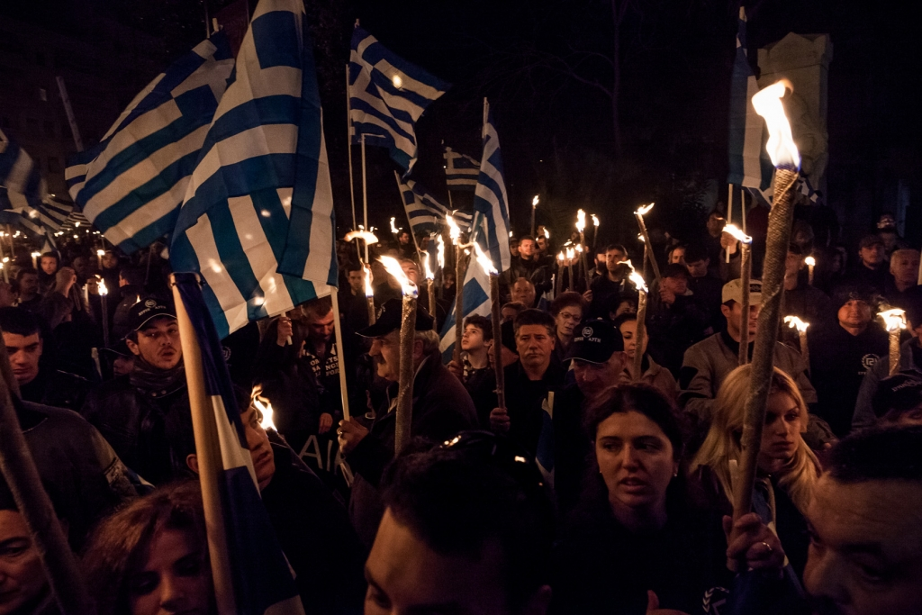 Supporters of the ultra nationalist Golden Dawn party hold Greek national flags and torches during a meeting in central Athens.