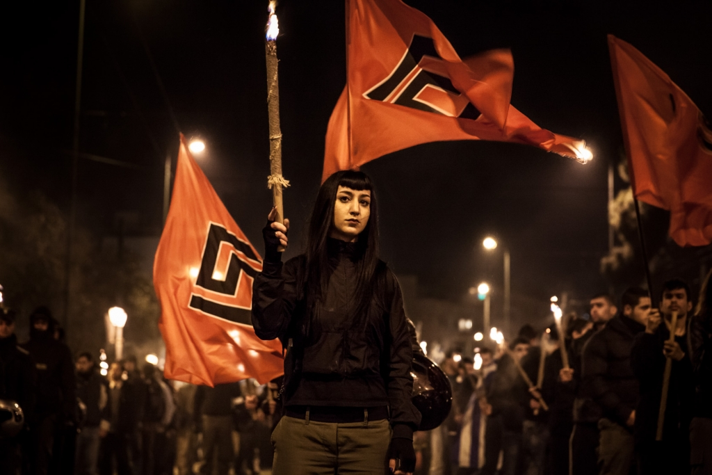 Supporters of the ultra nationalist Golden Dawn party hold flags and burning torches during a meeting in central Athens.